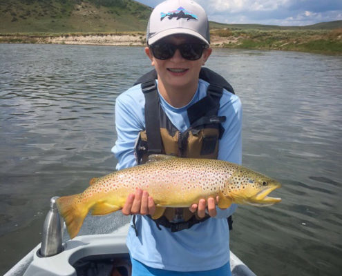 Boy holds cutthroat trout on the Snake river