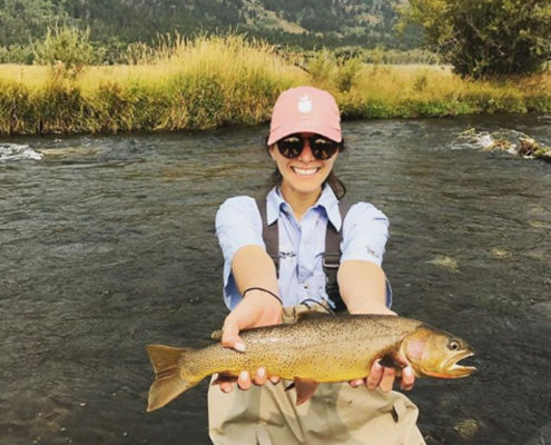 Woman fly fisherman holds cutthroat trout