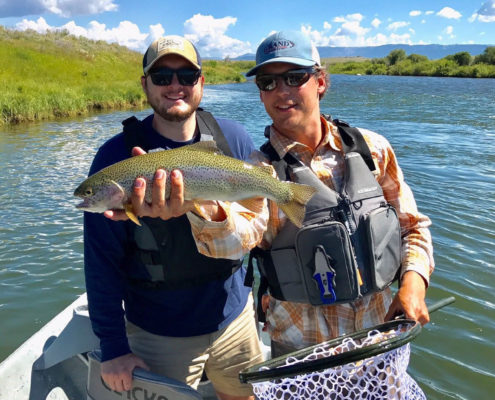 Fly fishing guide and client hold a rainbow trout on the green river wyoming